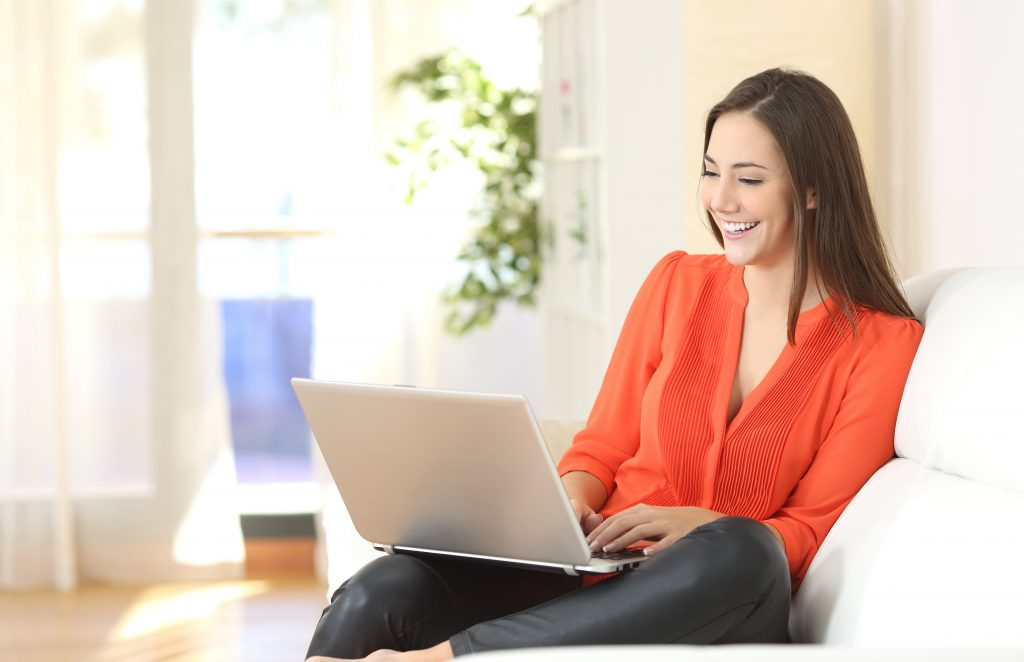 A woman typing on a laptop while sitting down
