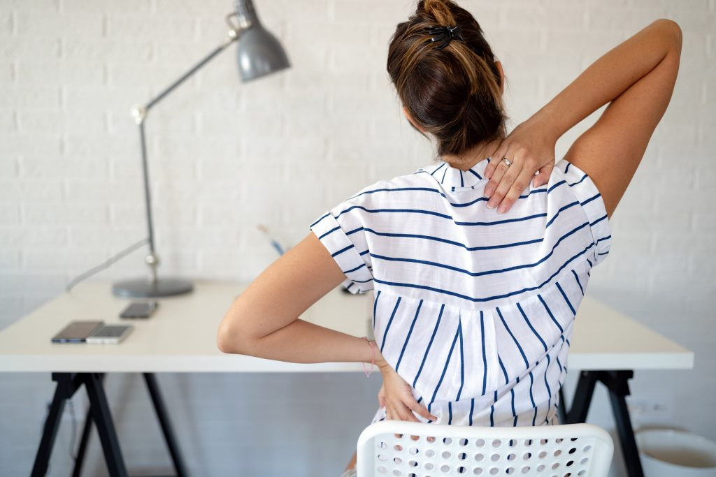 A woman sitting down at a desk, with both hands on her back in pain